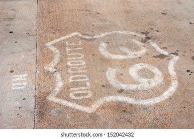 Old Route 66 sign on concrete road with oil spots