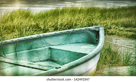 Old rowboat on the beach in the dune grasses, Bass River,  Cape Cod Massachusetts, USA. Vintage retro feel.