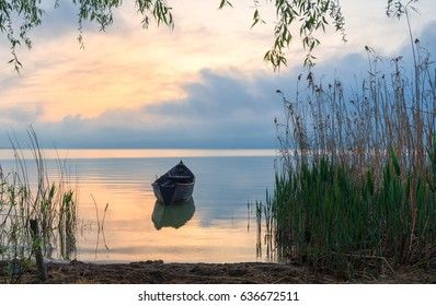 Old rowboat on the lake at sunset