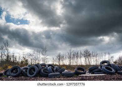Old rubber tires dumped and polluting nature, dark cloudy sky background