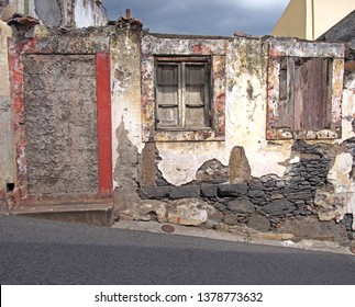 an old ruined house partly collapsed on a street with a blocked up door crumbling walls and fading red painted windows with closed shutters