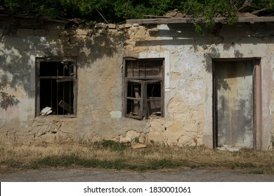 Old ruined house in a small village in distant rural area. Broken windows and door.  Adadonned home made from stone and bricks.