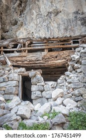 Old, ruined, stone building with door opening and exposed, decaying timber roof and limestone rockface behind, Ruta del Cares, Spain