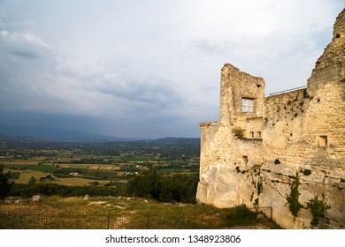 Old ruined stone walls with a window of the Castle of Marquis de Sade in Lacoste, Provence, France. Provence countryside in the background.