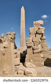 Old ruins with an obelisk with hieroglyphs on the blue sky background in Luxor in Egypt. Sun shines onto them. Vertical.
