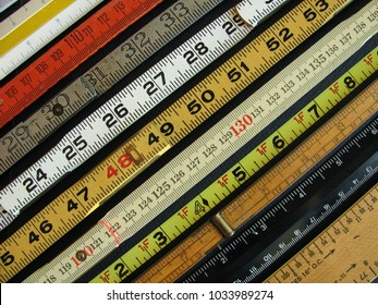 Old rulers both metric and inches, scales and measuring tools represent measurement, metrics, precision, accuracy and results.