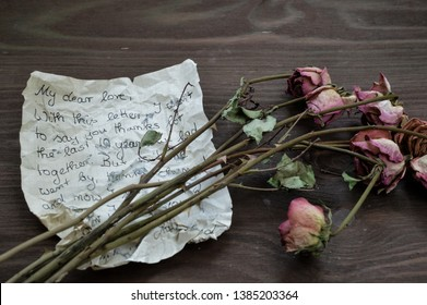 old rumpled farewell letter with withered roses on brown wooden table