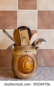 An old rumtopf jar used as kitchen utensil storage on a granite worktop with brown abd beige tiles in the background