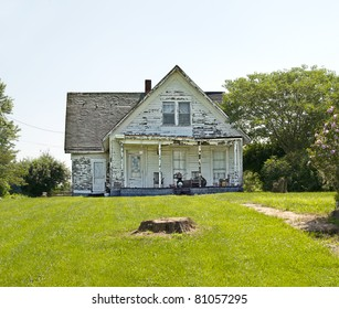 An old run down, weather beaten wood siding house that is in need of repair.  What a realtor would refer to as a fixer-upper.