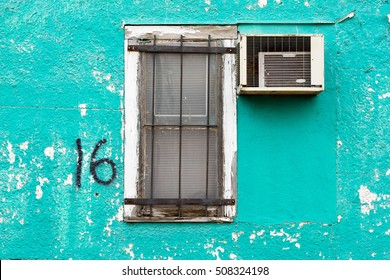 Old, Run Down Window in Aqua Blue, Stucco Wall with Broken Air Conditioner.
