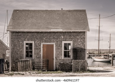 Old rundown fishing shack with lobster traps and boats in the background in a quaint New England coastal village.