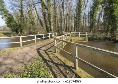 Old rundown wooden bridge over the brook the Boven-Slinge near Winterswijk in the Achterhoek in the early spring in the Netherlands
