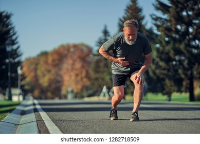 The old runner feeling bad while jogging