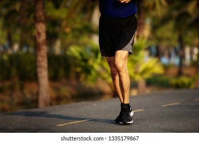 old runner feet running on asphalt road closeup