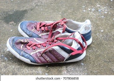Old running shoes with holes in them
