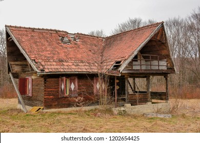 Old rural abandoned wooden collapsing house against cloudy sky in autumn season