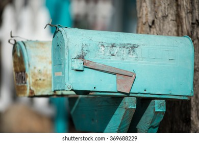 old rural blue mailboxes against a tree with a picket fence in background