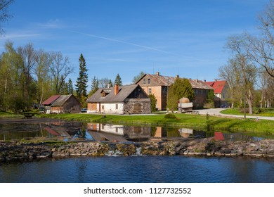 Old rural farmhouses near a pond at summer day