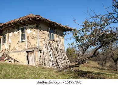 Old rural house with wood leaning against the wall