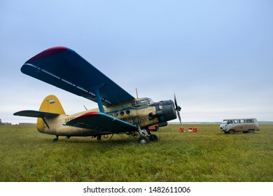 Old russian biplane aircraft An-2 on a green field. Soviet aircraft biplane Antonov AN-2 parked on a green grass of airfield against cloudy sky. Russia. Tatarstan. 3 October 2017.