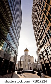 Old russian church between two modern skyscrapers. May be used as contrasts concept.