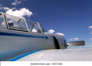 Old Russian fighter plane against a blue cloudy sky, now used for aerobatic displays.