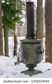 Old Russian samovar with a pipe is on white snow in a pine forest.