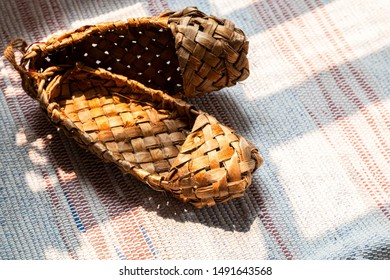 Old Russian sandals made of bark. Birch bark shoes, traditional old Russian shoes lie on an old traditional carpet in the sun.