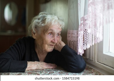 Old russian woman sits in a house near the window.