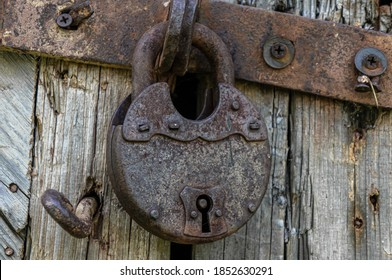 Old rust lock on the door. Metal lock on the gate of an old farmhouse. True village style. Rust steel latch locked with iron lock