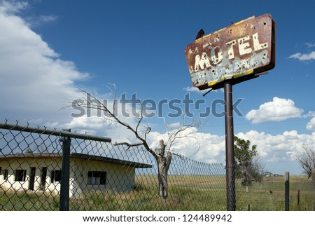 Old, rust motel sign with bullet holes, with a creepy tree, gutted building, and storm clouds in the background in a forgotten town in eastern Colorado.