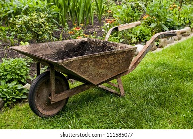 Old rusted barrow in garden