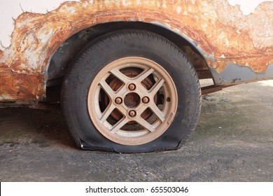 Old rusted car is a flat tire.