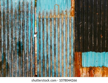Old rusted corrugated blue gate, grungy texture or background. Gate shut with a lock.