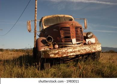 An old rusted farm truck in a field.