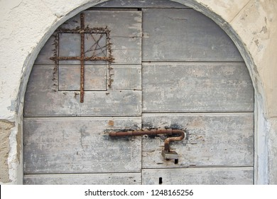 Old rusted latch/lock on gray painted wooden door in Vieste, Italy
