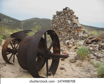 Old, rusted line shaft probably used in the stamp mill for mining gold.  One remaining stone wall of a structure in the distance.  Delamar, Nevada. 2009.