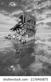 Old Rusted Shipwreck Peter Iredale on Pacific Ocean Beach, Beautiful Sunset Sky, Full Moon and Reflection in Black and White