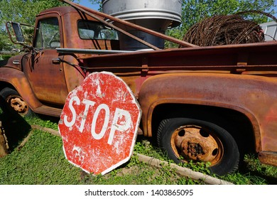Old rusted worn out truck with battered stop sign