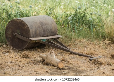 Old rustic abandoned derelict iron garden roller at edge of rural countryside field meadow still life