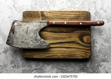 Old rustic axe for meat on a wooden board on grunge background. Food photography
