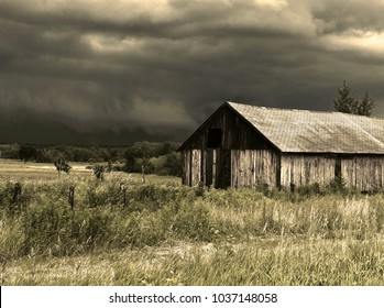Old rustic barn countryside landscape. Stormy skies. Tall grass.