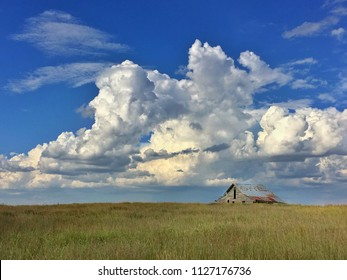 Old rustic barn in a wide open field under a huge blue sky and huge white thunder clouds in Oklahoma