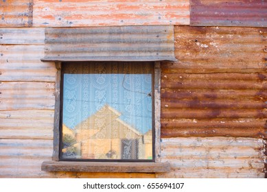 Old rustic corrugated iron walls of abandoned vintage house with broken glass window.