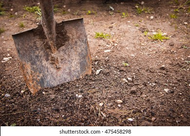 old rustic gardening tool stuck in the ground