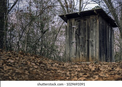 An old rustic outhouse on a hill. A nice composition with a rustic and outdoorsy design. foreground is out of focus with the background in focus.