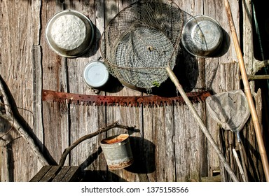 Old rustic pans and fishing nets hang outside of a rural cabin