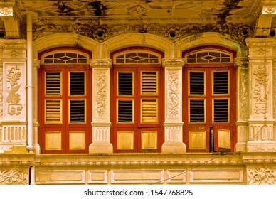 Old rustic peranakan style chinese shophouse with wooden shuttered windows.