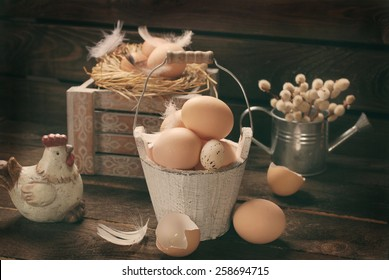 old rustic still life with eggs in vintage wooden bucket  and in nest for easter
