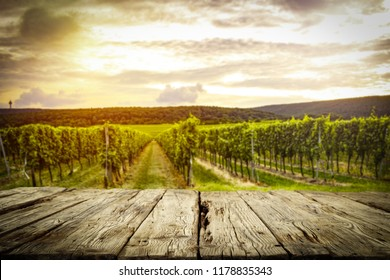 old rustic table in a beautiful vineyard at sunset